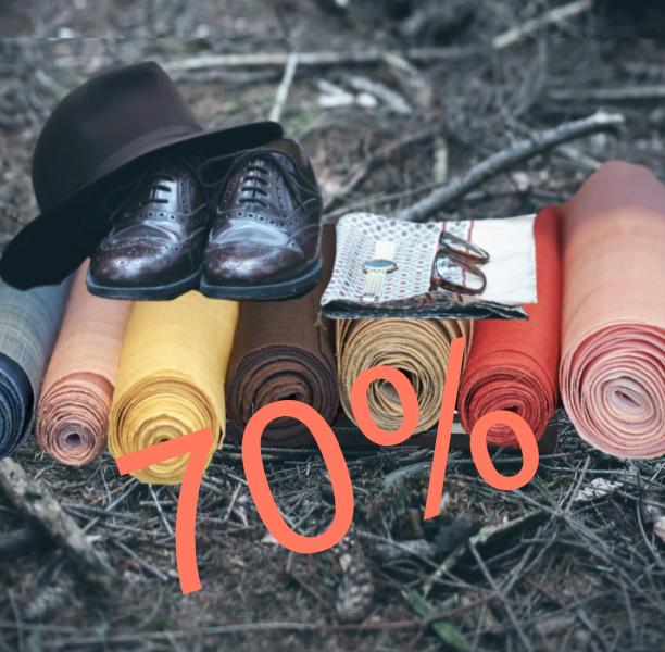 Im Wald auf dem Boden liegen ein Hut, Schuhe, Zeitung Brille und eine Uhr. Das alles liegt auf Stoffballen in verschiedenen Farben.